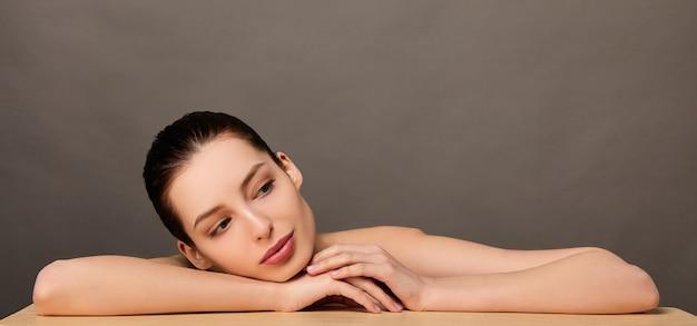 Портрет красоты молодой женщины, позирующей руками и лицом над поверхностью на светло-коричневом фоне