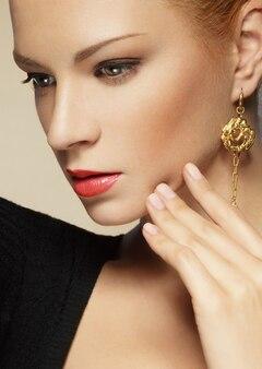 黄金の宝石を身に着けている若い女性の美しさの肖像画