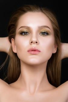 美しいメイクを持つ若い女性の美しさの肖像画。黄金のスモーキーな目。