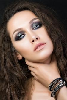 ファッションメイクアップを持つ若い女性の美しさの肖像画。
