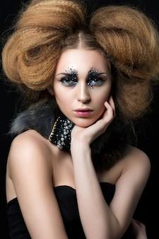 彼女の顔にラインストーンが触れているファッションメイクと若い女性の美しさの肖像画..カーニバルまたはパーティーメイク