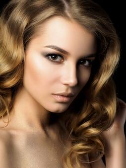 黄金のメイクで若い女性の美しさの肖像画。完璧な肌とファッションメイク、スモーキーアイ。官能性、情熱、流行の豪華なメイクのコンセプト。