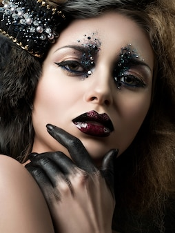 ラインストーンとモダンなファッションメイクで若い女性の美しさの肖像画..カーニバルやパーティーメイク