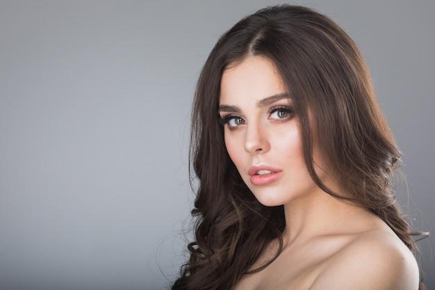 Красота портрет молодой женщины с голым плечом на серой стене