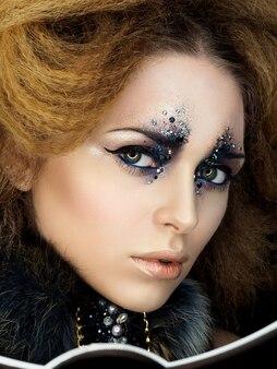 レトロなスタイルの若い女性の美しさの肖像画は、ラインストーンでメイクをファッションします。