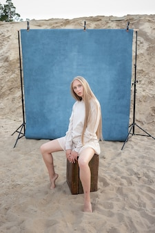 Beauty portrait outdoors on sand in front of blue background, pretty female posing. attractive caucasian girl with long hair looking at camera.