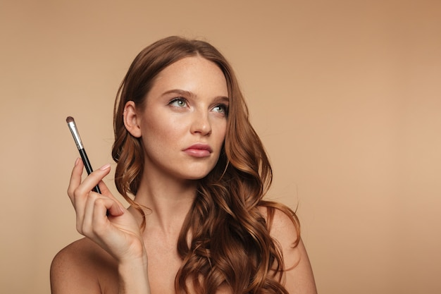 Beauty portrait of pensive ginger woman with long hair looking up while holding cosmetics brush