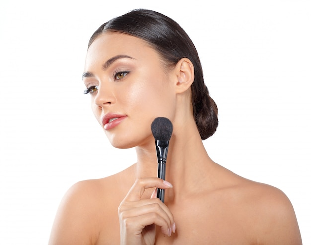Beauty portrait of a playful beautiful half naked woman applying make-up with a brush