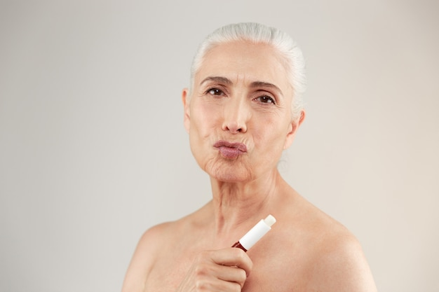 Beauty portrait of a playful half naked elderly woman