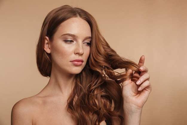 Beauty portrait of pretty ginger woman with long hair touching her hair and looking away