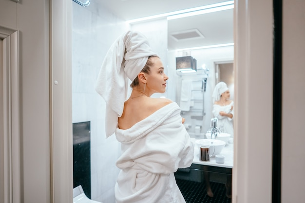 Beauty portrait of pretty woman dressing a white bath towel