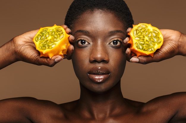 Beauty portrait of pretty young half-naked african woman holding kiwano horned melon isolated on brown
