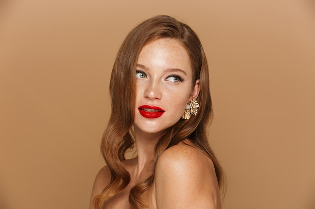 Beauty portrait of a pretty young  woman with long red hair wearing accessories posing isolated over beige wall