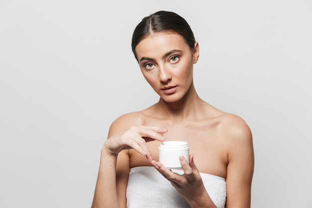 Beauty portrait of a pretty young woman wrapped in towel standing isolated, applying body cream from a container