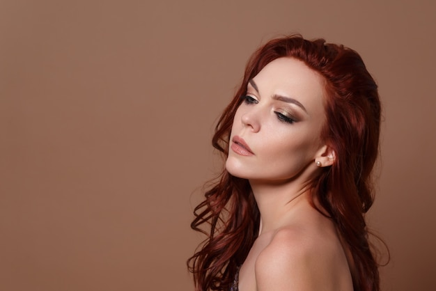Beauty portrait of a red-haired beautiful woman on a beige background. place for copyspace.