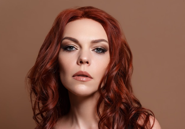 Beauty portrait of a red-haired beautiful woman on a beige background..