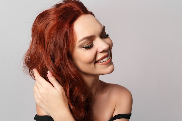 Beauty portrait of a red-haired happy beautiful woman on a gray background.