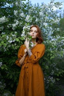 사과 나무의 가지에 봄에서 아름다움 초상화 빨간 머리 여자