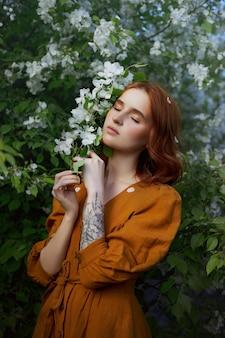 リンゴの木の枝に春の美しさの肖像画赤毛の女性