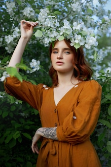 Beauty portrait redhead woman in spring in the branches of an apple tree Premium Photo