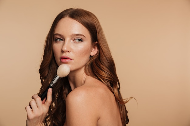Beauty portrait of sensual ginger woman with long hair posing sideways while looking away and holding cosmetics brush