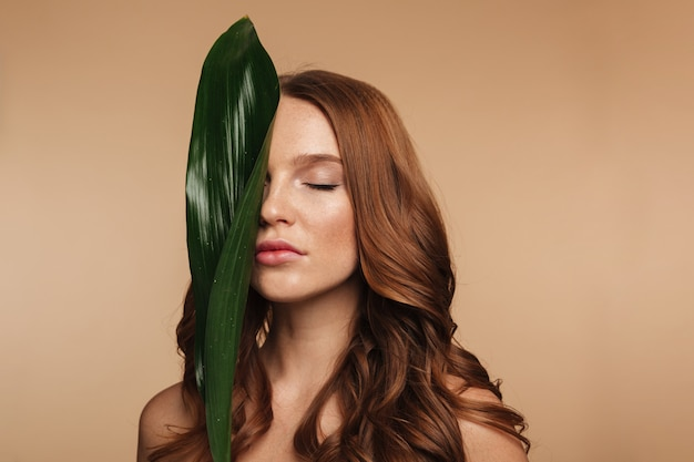 Beauty portrait of sensual ginger woman with long hair posing with green leaf