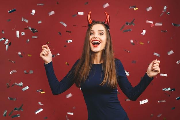 美しさの肖像画のセクシーな悪魔の女性。美容ファッションモデルの女性の顔。紙吹雪で赤い背景に対して隔離されるかなり悪魔。