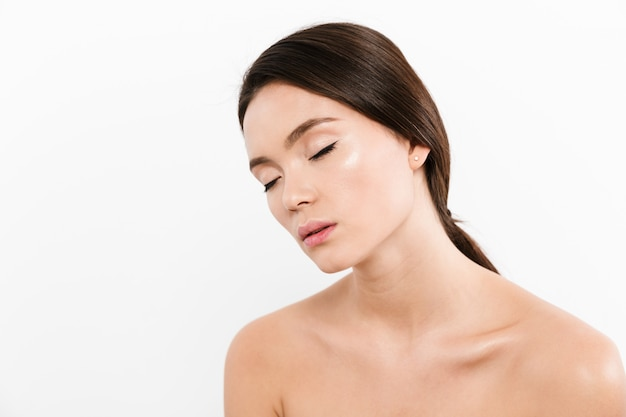 Beauty portrait of shirtless asian woman having brown hair in ponytail relaxing with closed eyes in half-turn, isolated over white