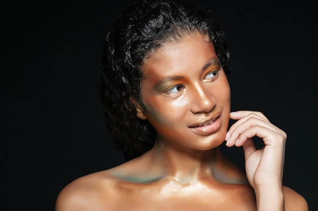 Beauty portrait of smiling american young woman with creative makeup over black