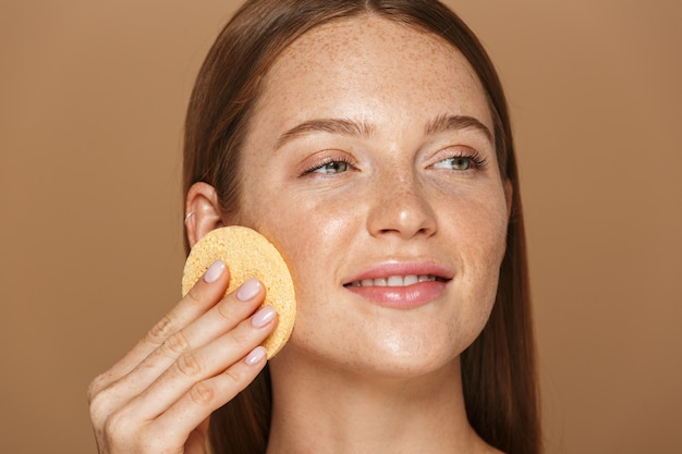 Beauty portrait of a smiling young topless woman with long red hair cleansing her face with a sponge isolated over beige wall