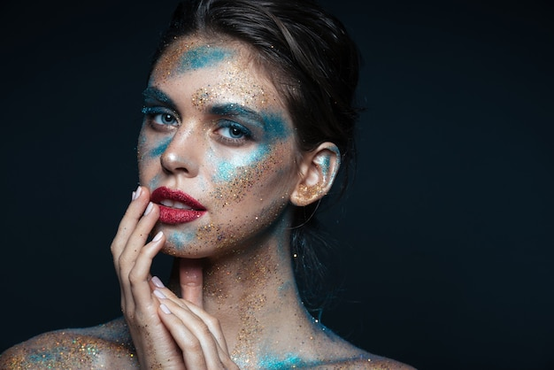 Beauty portrait of tender young woman with shimmering makeup touching her lips over black surface