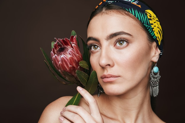 Beauty portrait of a topless young beautiful woman wearing headband and earrings standing isolated over black