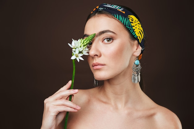 Beauty portrait of a topless young beautiful woman wearing headband and earrings standing isolated, posing with a flower