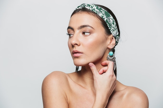 Beauty portrait of a topless young beautiful woman wearing headband and earrings standing isolated
