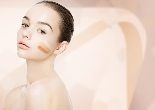 ピンクベージュの背景にファンデーションストライプ異なるトーンのメイクアップの美しさの肖像画