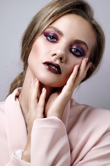 Beauty portrait of woman on gray wall, fashion model in pink jacket with clean skin and beautiful lips, make up deep purple smokey eyes