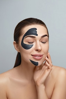 Beauty portrait woman skin care health black mask on grey background close up. girl model with cosmetic moisturizer spa facial mask