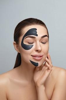 회색 배경에 아름다움 초상화 여자 피부 관리 건강 검은 마스크를 닫습니다. 화장품 보습 스파 페이셜 마스크가있는 소녀 모델