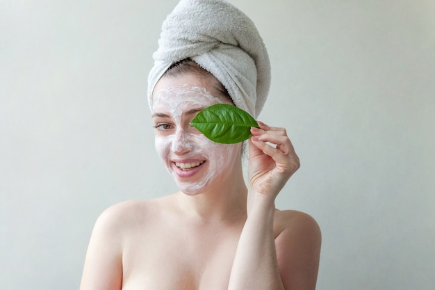 Beauty portrait of woman in towel on head with white nourishing mask or creme on face and green leaf in hand, white background isolated.