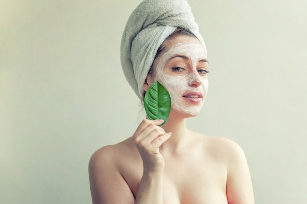 Beauty portrait of woman in towel on head with white nourishing mask or creme on face and green leaf in hand, white isolated. skincare cleansing eco organic cosmetic spa concept