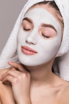 Beauty portrait of woman in towel on head with white nourishing mask or creme on face, white wall isolated. skincare cleansing eco organic cosmetic spa relax concept