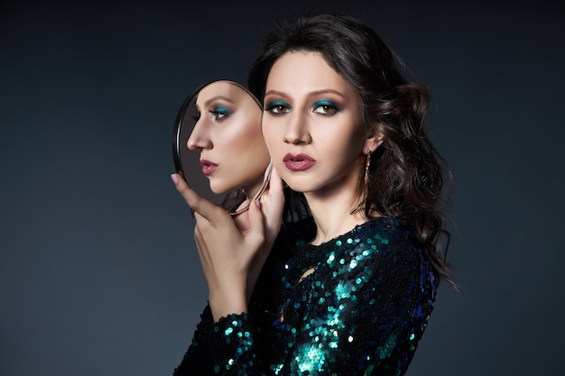 Beauty portrait of a woman with beautiful evening makeup and a mirror in her hands