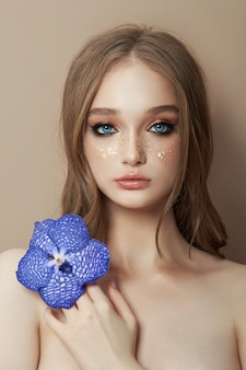 Beauty portrait of a woman with a blue vanda orchid in her hand.