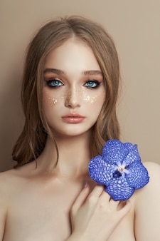 Beauty portrait of a woman with a blue vanda orchid in her hand
