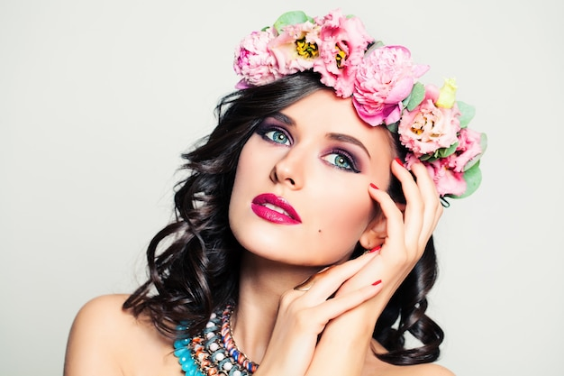 Beauty portrait of woman with nails painted, a flower crown and a necklace on white background