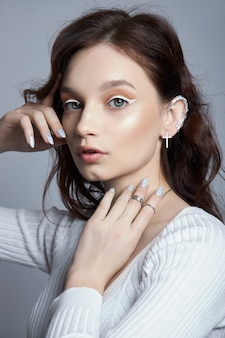 Beauty portrait of a woman with natural makeup and painted polished nails on her hand. rings on the fingers of the hand
