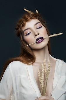 Женщина портрета красоты с косичкой на голове и колосьях пшеницы. яркая темная помада и макияж глаз, гладкая кожа лица