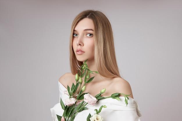彼女の手にピンクのトルコギキョウの花を持つ美しさの肖像画の女性。顔や体のスキンケアのための天然化粧品。白いシャツを着た美しい少女