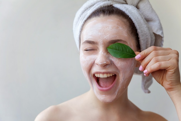 Beauty portrait of woman with white nourishing mask or creme on face and green leaf in hand