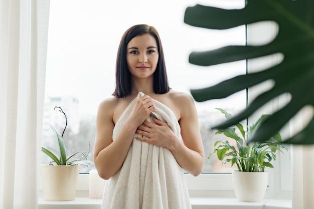 Beauty portrait of young brunette woman in bath towel